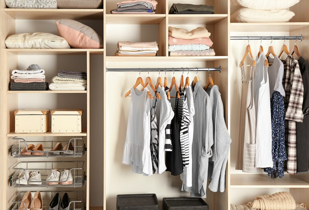 Large organised wardrobe closet with different clothes and shoes