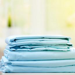 Folded bedsheet. Perfectly folded bedsheets. Bedsheet.
